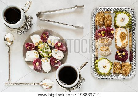 Eastern sweets. Assorted traditional Turkish delight (Rahat lokum) on gray stone background. Turkish delight with different nuts coconut shavings coffee in cups spoons tongs for sweets. Top view