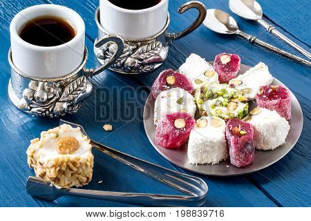Eastern sweets. Assorted traditional Turkish delight (Rahat lokum) on blue wooden background. Turkish delight with different nuts and coconut shavings coffee in cups spoons and tongs for sweets