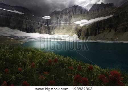 Rays of sun hitting the stunning turquoise colored water at the base of Grinnell Glacier in Glacier National Park Montana