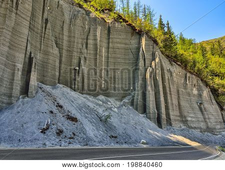 Vertical higher wall from compressed sand above the road which is destroyed by wind and precipitation and forms fanciful poles Altai Russia