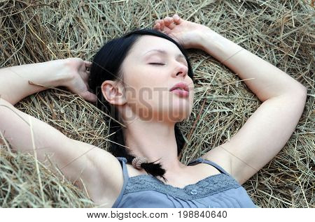 young attractive woman sleep on the haystack in summer day