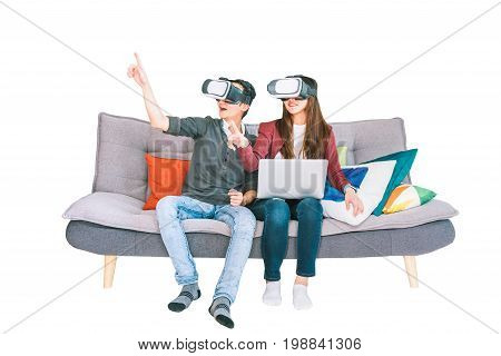Young Asian couple playing VR virtual reality gadget sitting on sofa together isolated on white background. Modern entertainment technology VDO game devices or family hobby activity concept