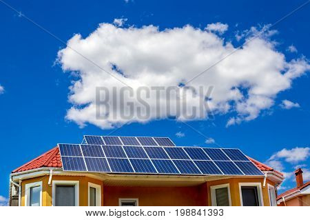 Solar panel on a red roof reflecting the sun and blue sky