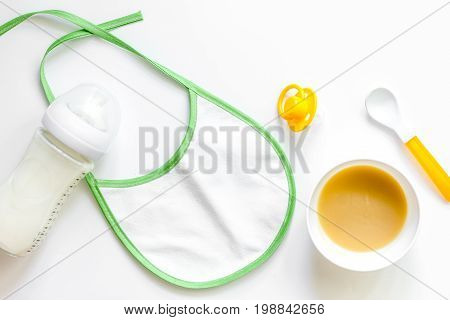 Preparing to feed baby. Puree, spoon and bib on white background top view.