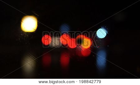 Night city in the lights of street lamps. Defocused view through the wet glass of the car