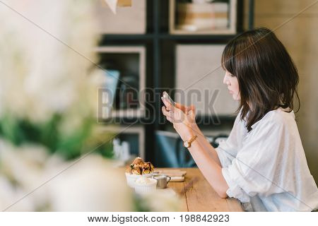 Beautiful young Asian girl using smartphone at cafe with chocolate toast ice cream and milk syrup. Coffee shop dessert and modern casual lifestyle or mobile phone technology concept. With copy space