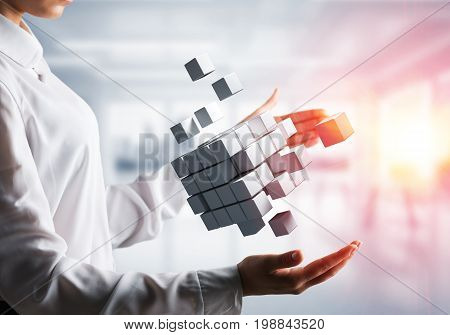 Cropped image of business woman hands holding multiple white cubes in hands with sunlight on office background. Mixed media.
