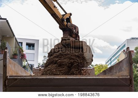 On a construction site bucket dredger works and loads rubble on trucks