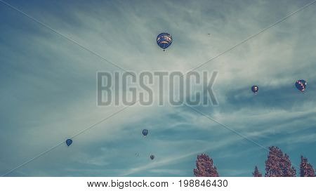 Bristol UK - August 13 2016: The Bristol International Balloon Fiesta 2016 showing the mass ascent and landings of over 100 balloons including special shapes and the 'night glow' where the burners are used at night to illuminate the balloons. This annual