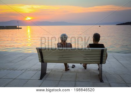 Two senior women enjoying the sunset on the bench at the waterfront in Njivice island Krk Croatia.