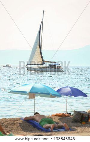 A sailboat sailing next to the beach in Njivice island Krk Croatia.