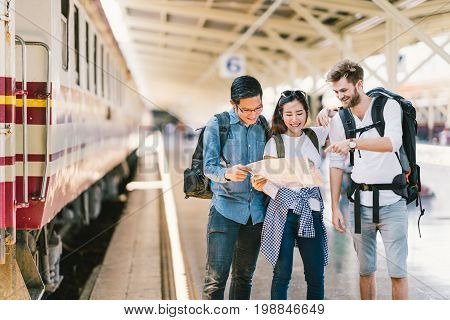 Multiethnic group of friends backpack travelers or college students using local map navigation together at train station platform. Asia travel destination tourism activity or railroad trip concept
