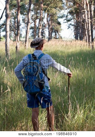 Caucasian Adolescent In Hat With Backpack And Stick Stands In The Forest. Summer Time.