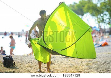 NJIVICE CROATIA - JUNE 24 2017 : A man wrapping the tent on the beach in Njivice island of Krk Croatia.