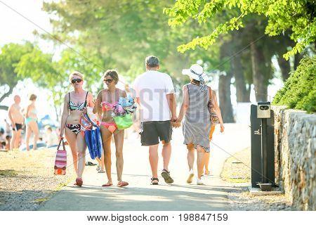 NJIVICE CROATIA - JUNE 24 2017 : People walking on the beach in Njivice island of Krk Croatia.