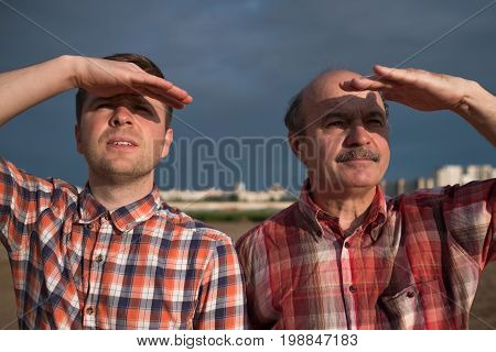 Casual middle aged men looking far away outdoor