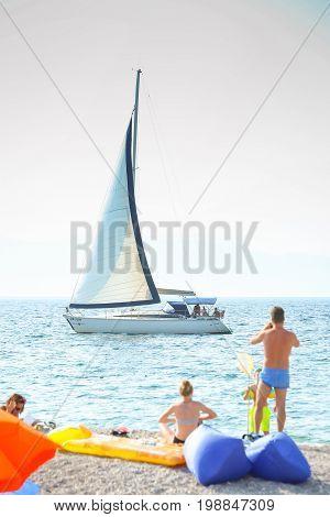 NJIVICE CROATIA - JUNE 24 2017 : A sailboat sailing next to the beach in Njivice island Krk Croatia.