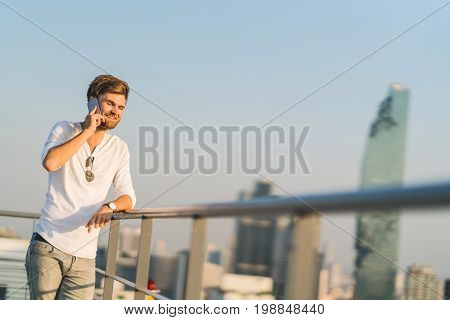 White man using mobile phone at rooftop during sunset smiling while on phone call. Communication or telecommunication technology concept. Sunset in city scene