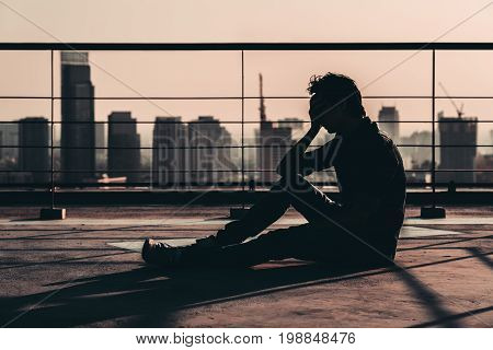 Silhouette of sad depressed young Asian man lost hope and cry sit on building rooftop at sunset dark mood tone. Concept of major depressive disorder friend zone unemployment stress emotion or paranoid