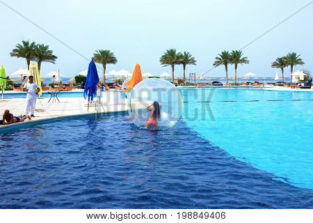 Sharm El Sheikh, Egypt - April 09, 2017: The girl in an inflatable balloon, having fun on the water at Sharm El Sheikh, Egypt - April 09, 2017. The ball in the water - fascinating summer attractions for children. Water zorbing.