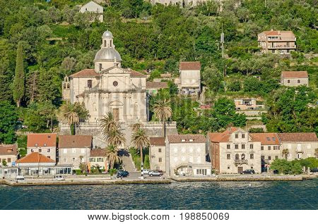Prcanj. The town's waterfront with a long line of stone villas and the most impressive feat of architecture in Prcanj - the Birth of Our Lady church designed by a Venetian architect Bernardino Maccaruzzi. The church has a monumental baroque facade with Co