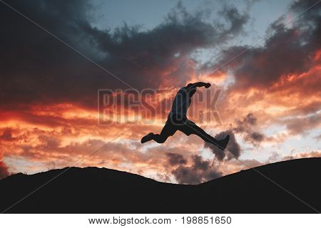 Male athlete engaged in parkour and freeran in the background of a beautiful sunset. Silhouette of a man at the moment of a jump