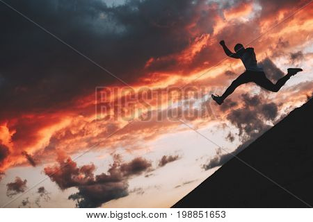 Silhouette of a brave male athlete jumping from the hill during a workout. Parkour and freerun