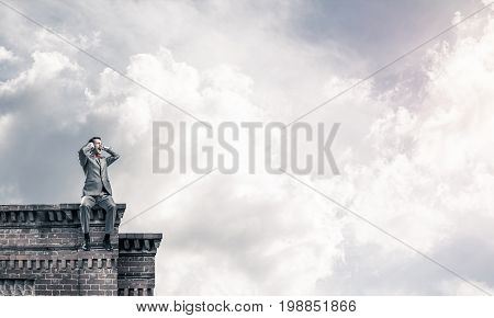 Frustrated businessman sitting on building top and closing ears with hands