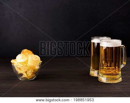 Two Glasses Of Beer And Chips And Peanuts On Wooden Dark Background, Copy Spase