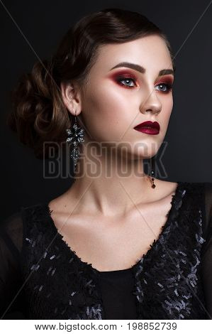 Portrait of beautiful young model with professional colorful makeup, perfect skin, red lips, retro hairdo in black clothes on dark background. Trendy colorful smoky eyes. Retro style