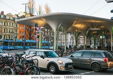 Image of U-Bahn or S-Bahn metro station with parking lot full of cars and bicycle, tram and buildings on the background.