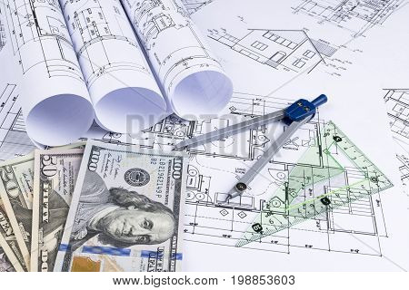 A blueprint of an architect with money. Symbolic photo for financing and planning of a new house. Blueprints rolls and a drawing instruments on the worktable