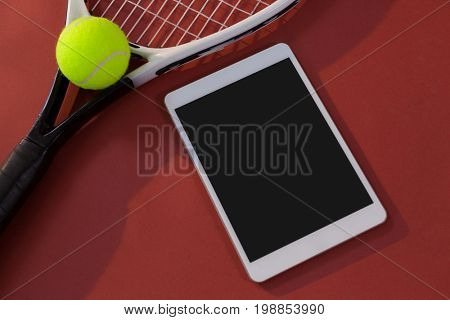 High angle view of tennis racket and ball by digital tablet on maroon background