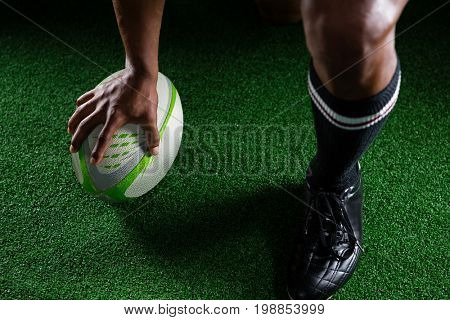 High angle view sportsman kicking rugby ball while standing on field