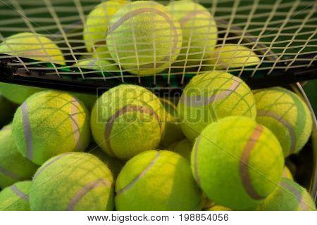 Close up of racket on tennis balls in bucket