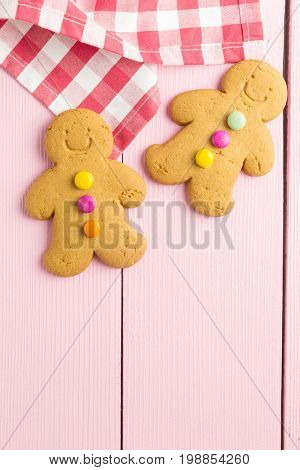 Two gingerbread men on colorful wooden table. Top view. Xmas gingerbread.