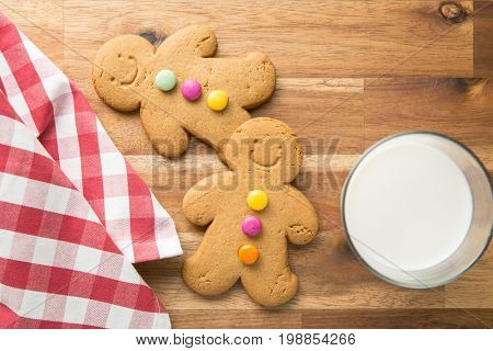 Sweet gingerbread men and glass of milk. Xmas gingerbread on wooden table.