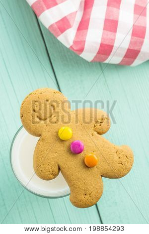 Sweet gingerbread man and glass of milk on wooden table. Xmas gingerbread.