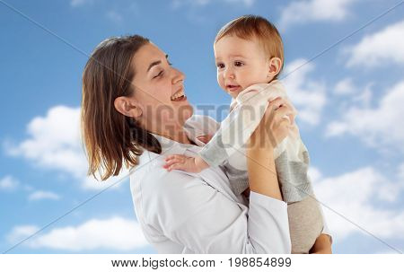 medicine, healthcare, pediatry and people concept - happy woman doctor or pediatrician holding baby over blue sky background
