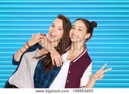 people, teens and friendship concept - happy smiling pretty teenage girls or friends hugging and showing peace hand sign over blue ribbed background