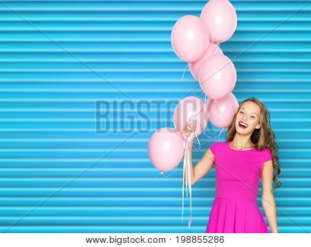 people, holidays and fashion concept - happy young woman or teen girl in pink dress with helium air balloons over blue ribbed background