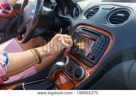 summer holidays, travel, road trip and people concept - young man driving car and turning toggle switch on dashboard
