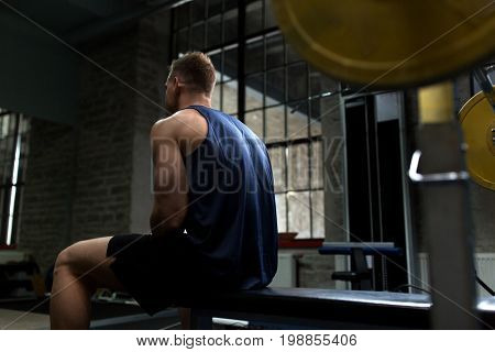 sport, bodybuilding, fitness and people concept - man sitting on weight bench in gym