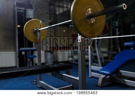 sport, fitness and equipment concept - weight bench with barbell in gym