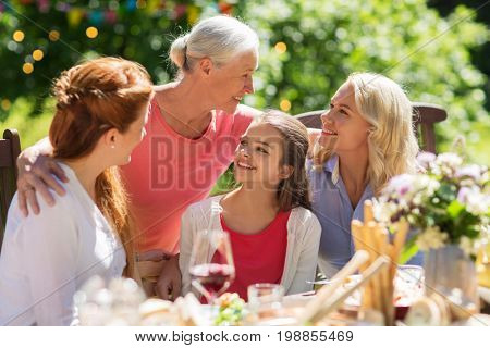 leisure, holidays and people concept - happy female family having festive dinner or summer garden party