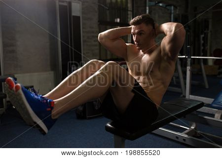 sport, fitness, bodybuilding, lifestyle and people concept - young man doing sit-up abdominal exercises in gym