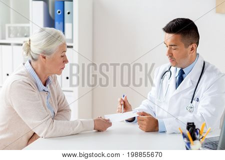 medicine, age, healthcare and people concept - senior woman and doctor with prescription or referral at hospital