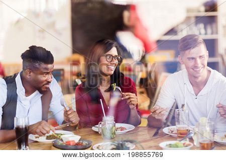 leisure, food and people concept - group of happy international friends eating at restaurant table (shot through window)