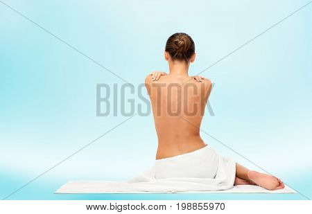 beauty, spa, people and bodycare concept - beautiful young woman in white towel with bare top from back over blue background