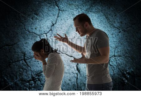 people, relationship difficulties, conflict and family concept - angry man abusing woman over cracked concrete background